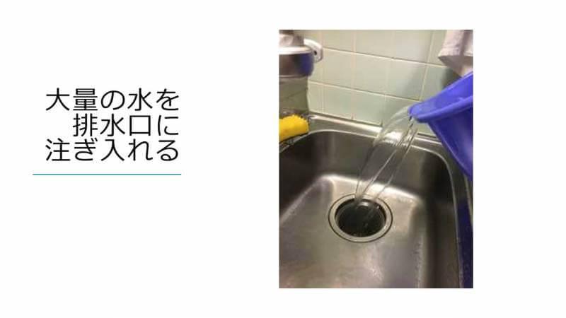 大量の水を排水口に注ぎ入れる